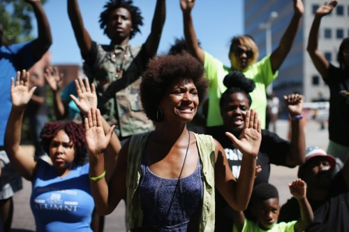 "Protestors in Ferguson, Missouri chant ""hands up, don't shoot!"""