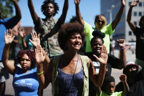 "Protestors in Ferguson, Missouri chant ""hands up, don't shoot!"""